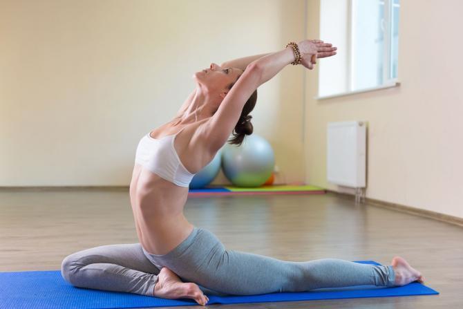 Yong kadın egzersiz yoga pose mat beyaz zemin üzerine izole